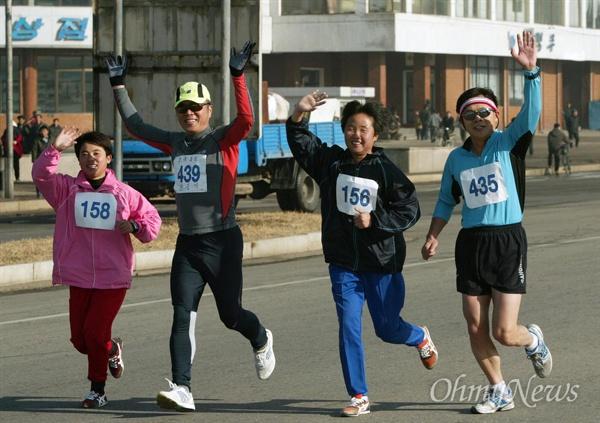 오마이뉴스 주최 '평양-남포 통일 마라톤대회`가 2005년 11월 24일 오전 평양 서산경기장에서 남북 선수 200여명이 참석한 가운데 성황리에 열렸다. 남북의 선수들이 평양시내를 달리며 손을 흔들고 있다.
