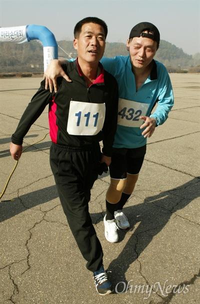 지난 2005년 11월 24일 오마이뉴스 주최 '평양-남포 통일 마라톤대회'에 참가한 한 남측(오른쪽) 유원진 선수가 코스 내내 함께 달리며 페이스 조절을 해준 북측 선수에게 감사 표시를 하며 결승지점인 서산축구경기장을 들어서고 있다.