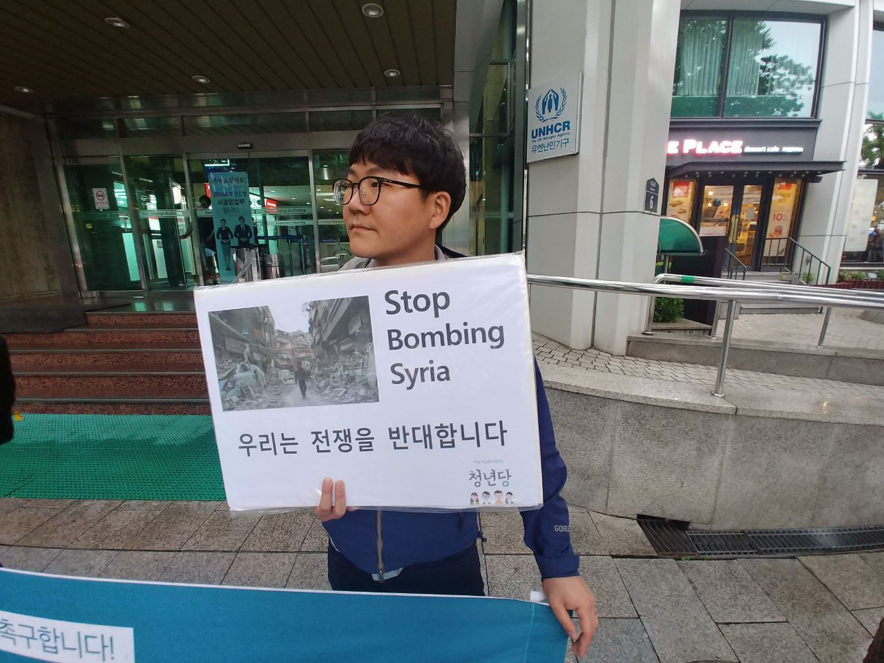 기자회견에 참석중인 권오민 청년 전쟁을 반대하는 피켓을 들고 기자회견 중