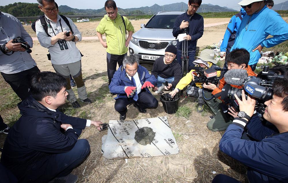 박창근 교수가 낙동강 한가운데 바닥에서 퍼온 저질토를 살펴보며 기자들에게 설명하고 있다