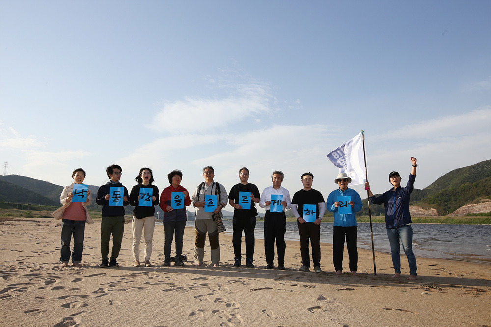 낙동강에서 지금 유일하게 자연성이 남아 있는 황강 합수부에 깨끗한 새로운 모래톱이 돌아왔다. 황강의 모래가 낙동강으로 대거 유입된 결과다. 그곳에서 활동가들이 피켓팅을 벌이고 있다.