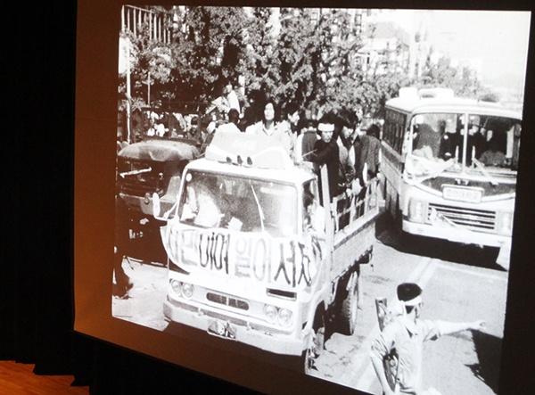 """5·18 당시 시위대가 차량을 타고 이동하는 모습. """"시민이여 일어서자""""라는 문구의 현수막이 차량 앞에 걸려있다."""