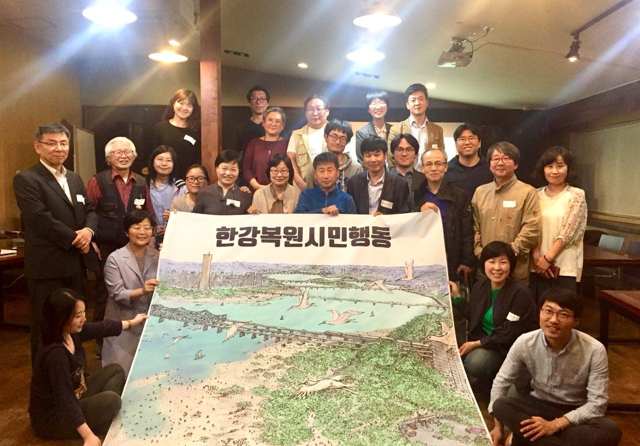 한강행동 한강복원시민행동 토론회에 참석한 참가자들이 행사 후 복원된 한강 미래도를 배경으로 사진을 찍고 있다.