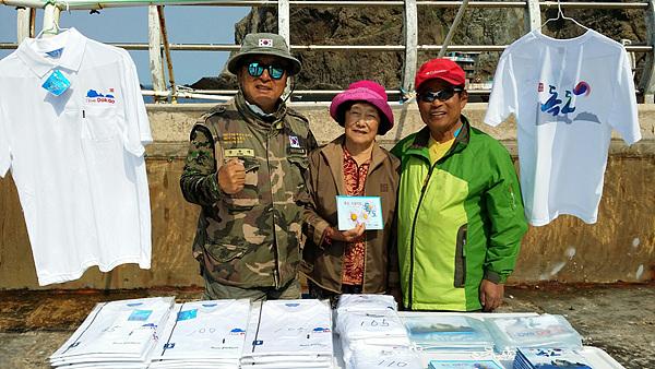 몇년전 독도에 상륙한 관광객들에게 독도기념품을 팔고 있는 김성도씨 부부와 정광태(맨 왼쪽) 가수. 정광태씨는 <독도는 우리땅>을 부른 가수다