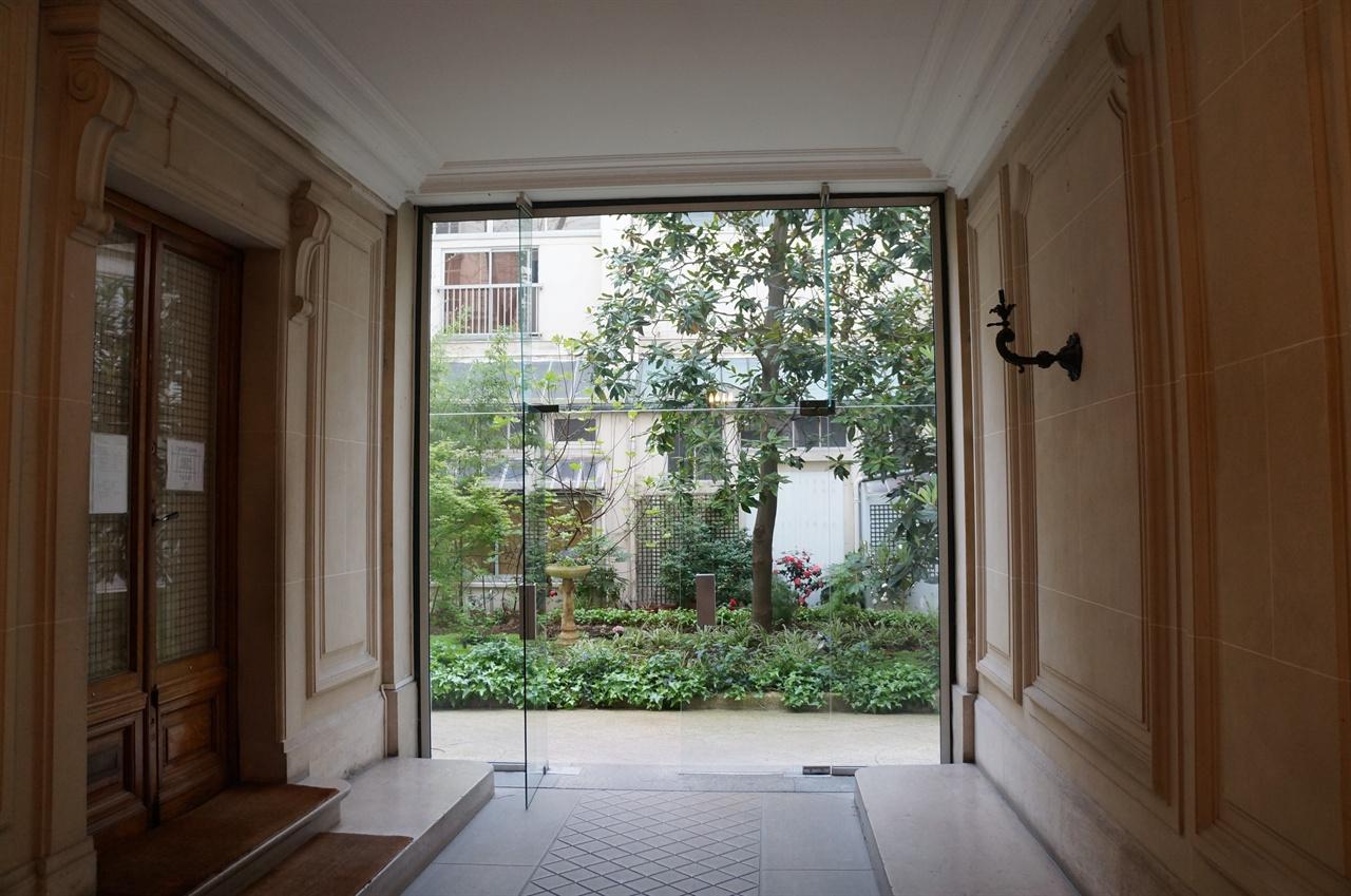 아파트 출입구 통로와 현관문 아파트 대문을 들어서면 안으로 통하는 통로가 있고, 좌측에 보이는 문이 '스타인 살롱'으로 들어가는 현관문이다. 통로 끝에는 건물 전체의 채광과 통풍을 위한 50평 정도의 옥내정원이 보인다.