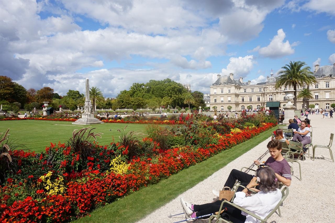 뤽상부르 공원 반쯤 드러누울 수 있게 만든 정원 앞 의자에 앉아 휴식을 취하고 있는 파리시민들. 오른쪽 뒤에 보이는 건물이 뤽상부르 궁전이다.