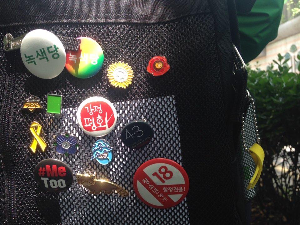 한진희씨 가방에 달린 뱃지들 강정평화, 미투, 동백꽃, 세월호 리본과 18세 선거권, 녹색당 등의 뱃지가 주렁 주렁 달려있다.