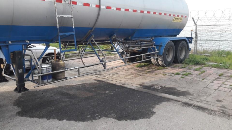 탱크로리 밑으로 흘러내린 기름으로 바닥에 흥건이 젖어 있는 모습