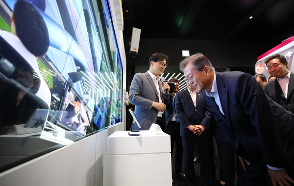 문재인 대통령이 17일 오후 서울 강서구 마곡 R&D 단지에서 열린 혁신성장 보고대회에서 SKT관계자로부터 설명을 들으며 5G를 이용한 스마트 미디어월을 체험하고 있다.