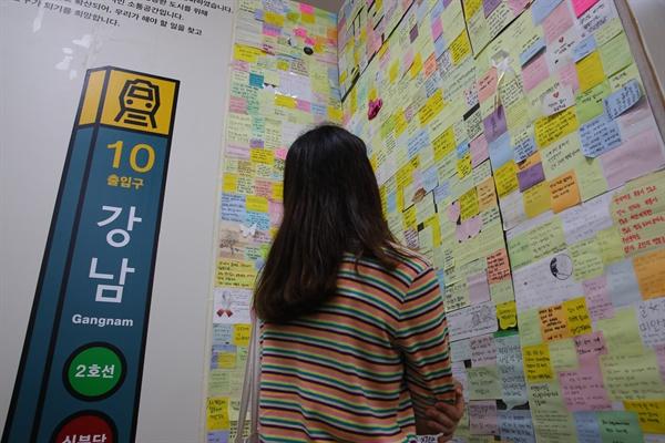 강남역 2주기, 기억의 발걸음 강남역 여성 살해사건 2주기를 맞은 17일 서울 동작구 여성플라자 성평등도서관 '여기' 안에 마련된 '기억ZONE:강남역 10번 출구'를 찾은 한 여성이 포스트잇 글들을 읽으며 피해여성을 추모하고 있다.