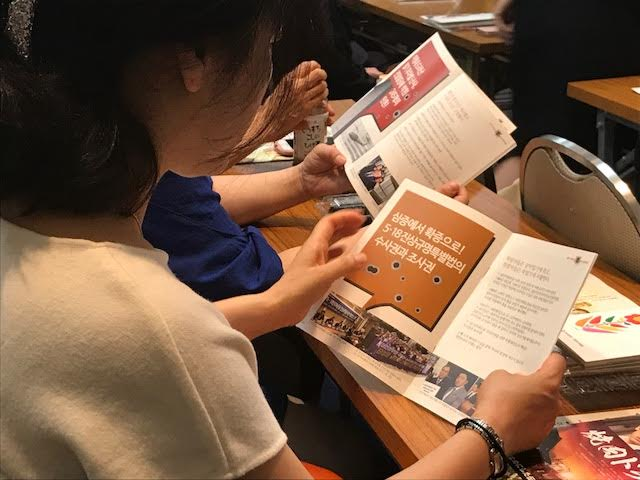 진상규명을 촉구하는 팜플렛을 보고 있는 참석자들