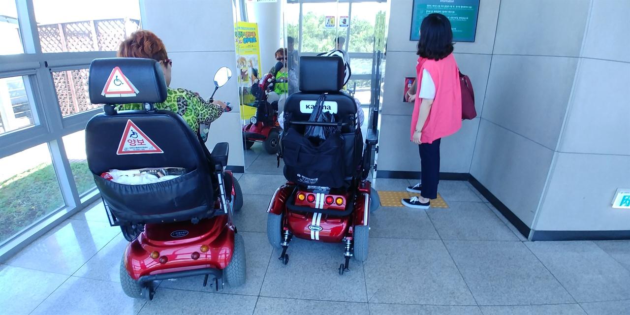 엘리베이터 앞에서 전동휠체어 장애인이 전동휠체어로 엘리베이터를 타려면 문이 닫히지 않도록 누군가 잡아줘야 한다.