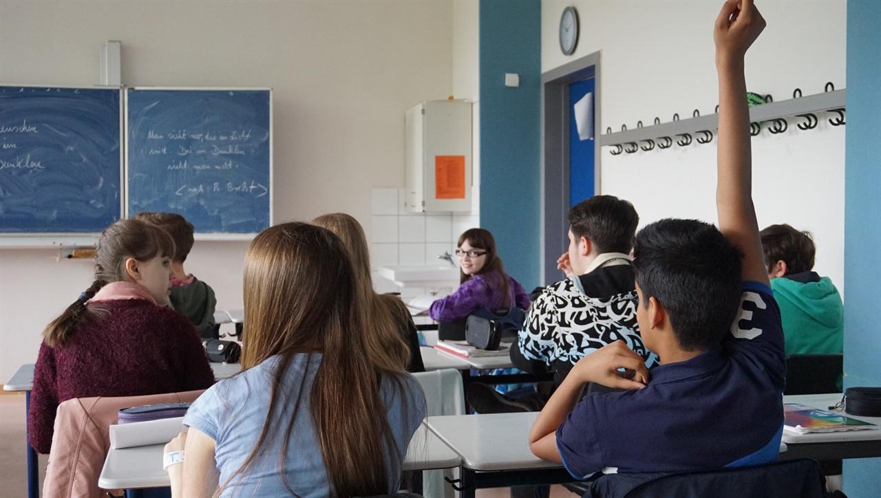 """""""제가 발표하겠습니다"""" 독일 비스바덴 딜타이김나지움의 독일어 시간에 한 학생이 교사의 질문에 답변하기 위해 손을 들고 있다."""