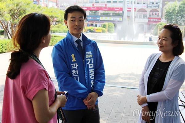 김종천 후보가 과천 중앙공원에서 시민들과 대호를 나누고 있다.