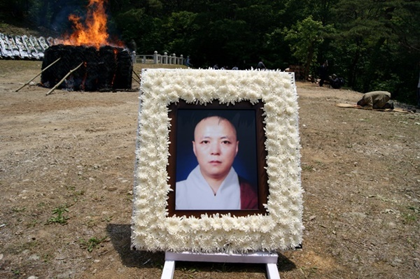 2010년 영결식 당시 스님의 다비장 앞에 내걸린 스님의 영정. 영남자연생태보존회 정제영 총무이사가 스님 다비장 앞에 추모의 절을 올리고 있다.