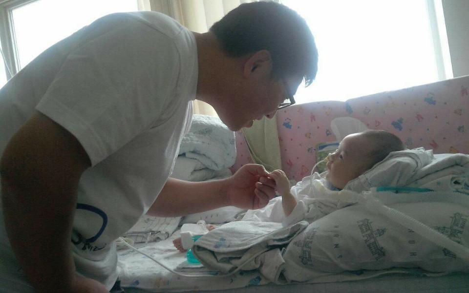강현이가 병원에 온 아빠와 반갑게 인사하고 있다
