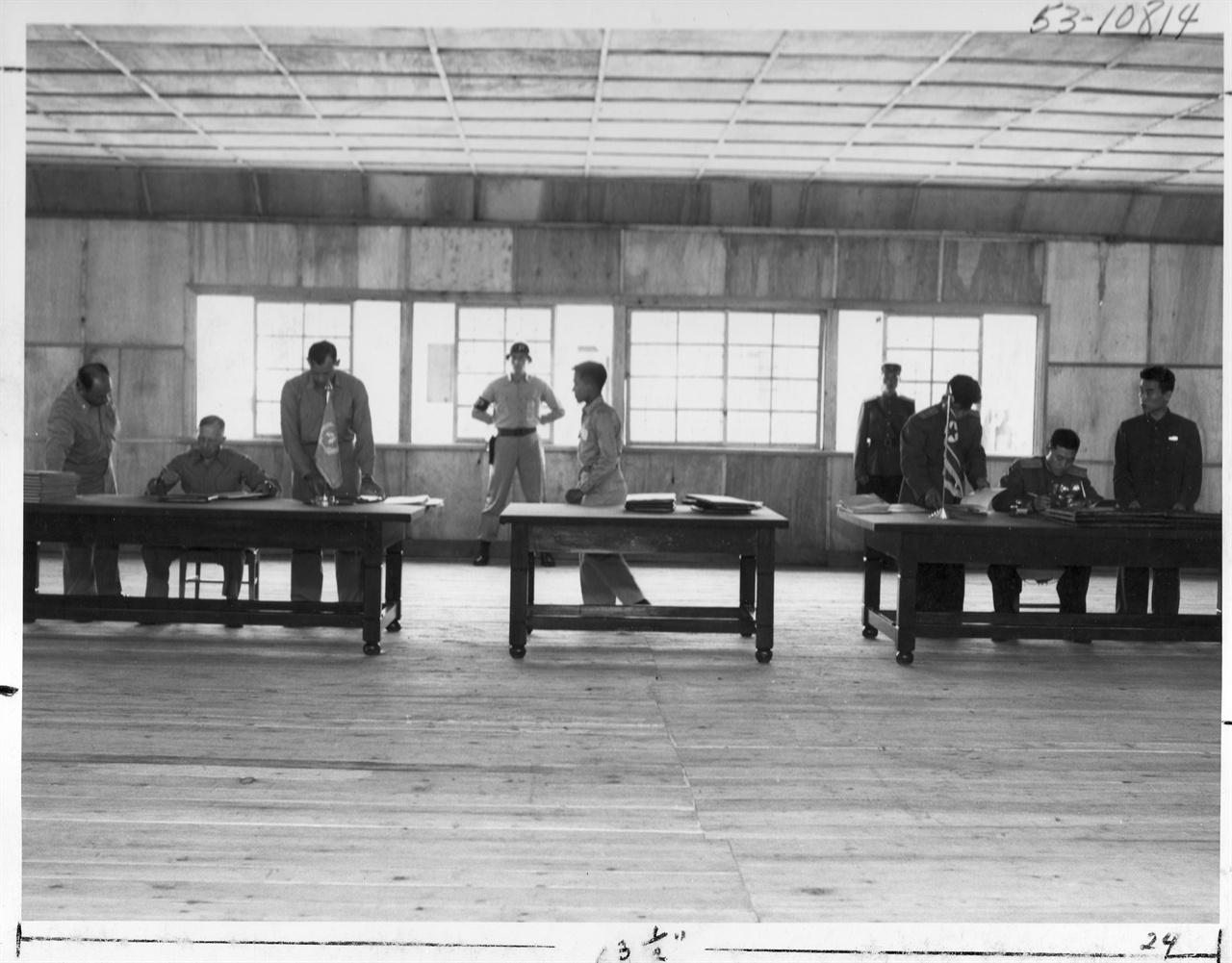 1953. 7. 27. 판문점, 정전회담 조인식으로 왼쪽 책상에서 유엔군 측 대표 해리슨 장군이, 오른쪽 책상에서는 북한 측 남일 장군이 서명하고 있다.