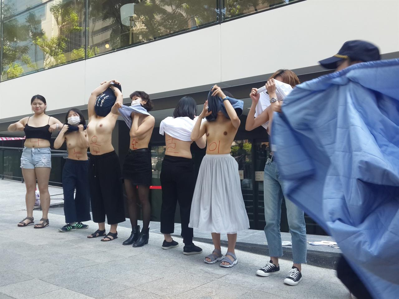 페이스북 사옥 앞에서 상의를 탈의하는 불꽃페미액션 회원들과 이를 급하게 제지하기 위해 이불로 가리러 달려오는 경찰들