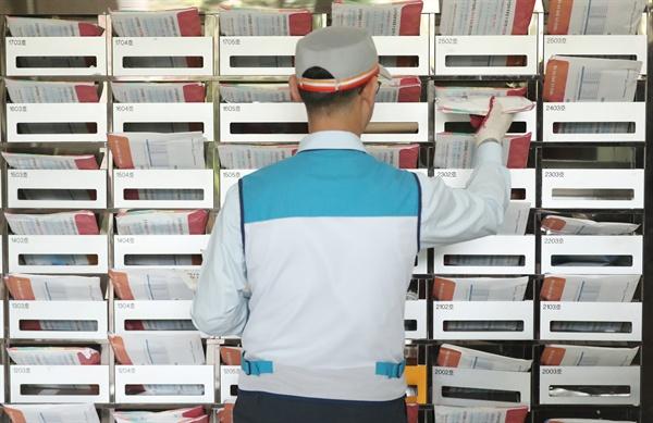 후보 정보 확인하세요  6·13 지방선거를 열흘 앞둔 3일 오전 서울 서초구의 한 아파트에서 집배원이 책자형 선거공보물을 우편함에 배달하고 있다.