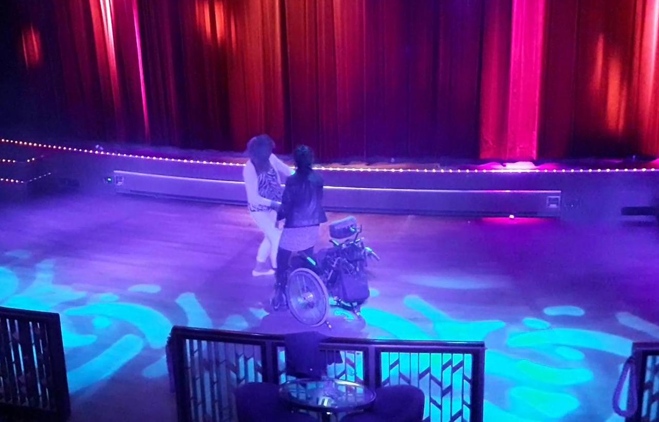 밴드가 쉬는 동안 휠체어 탄 여성과 그 보호자가 스테이지에 나와 춤을 추고 있다. (스웨덴 스톡홀름에서 핀란드 헬싱키로 향하는 크루즈 나이트클럽에서)
