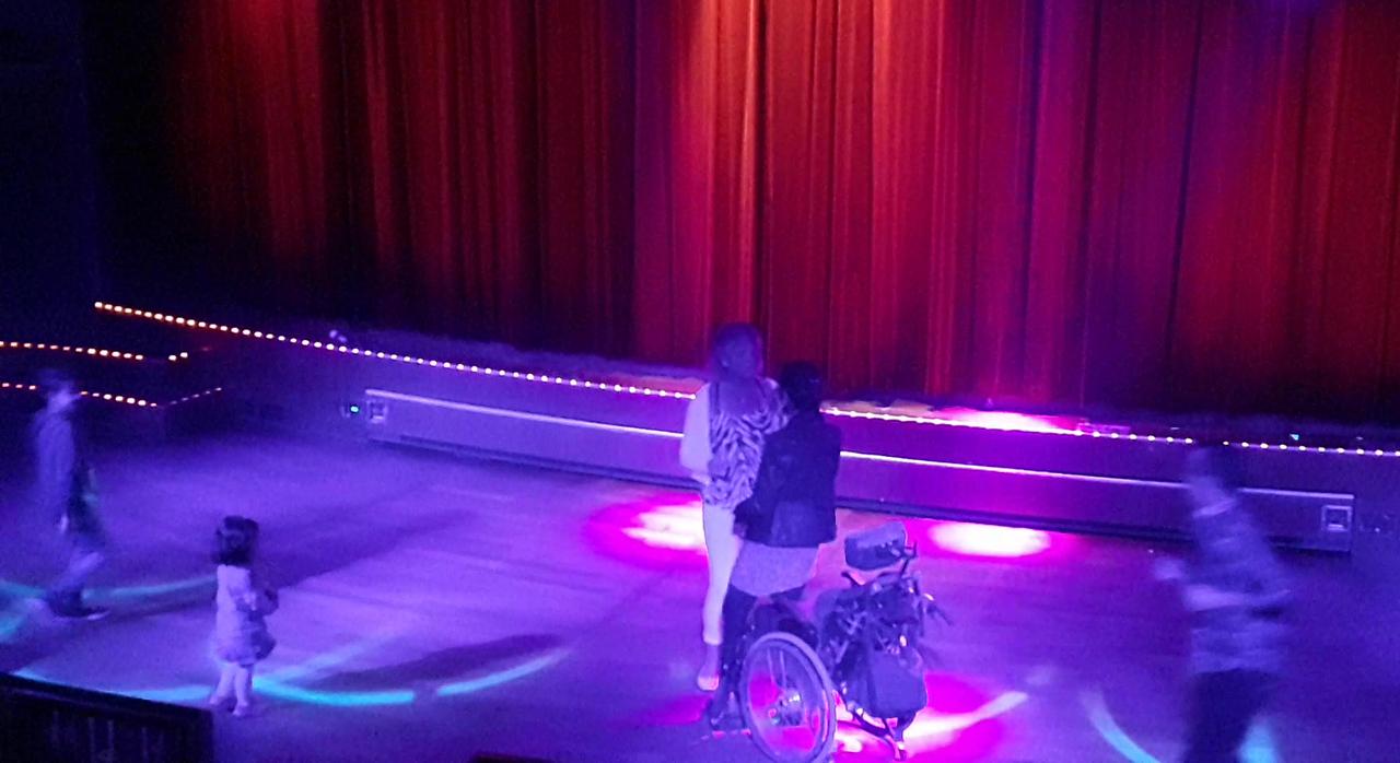 휠체어 탄 여성과 그 보호자가 춤을 추자 어린이와 함께 한 청년이 스테이지로 나오고 있다. (스웨덴 스톡홀름에서 핀란드 헬싱키로 향하는 크루즈 나이트클럽에서)