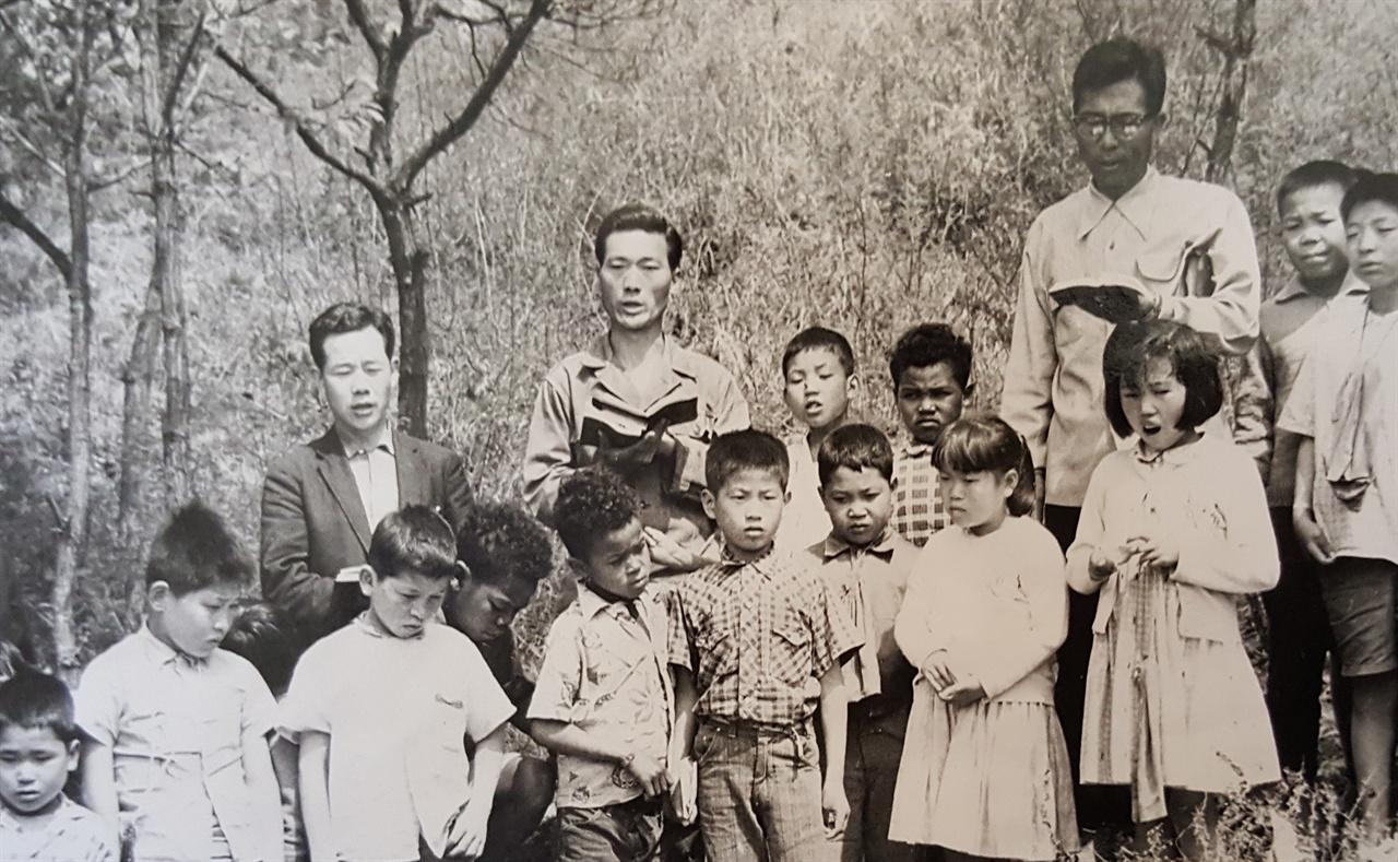 """일산 홀트 복지원에서 원우들과 함께, 정중앙에 체크무늬 셔츠를 입은 소년이 스티브 모리슨 입양되기 전 6세~14세까지 스티브 모리슨은 홀트 부부가 세운 일산의 홀트복지원에서 자랐다. 나중에 이곳에 방문했을 때, 입양되지 못한 채 이곳에 남았던 친구들을 만나고 이야기를 들으며 스티브는 수없이 물었다. """"왜 나는 선택받았고, 이 친구들은 선택받지 못했나?"""""""