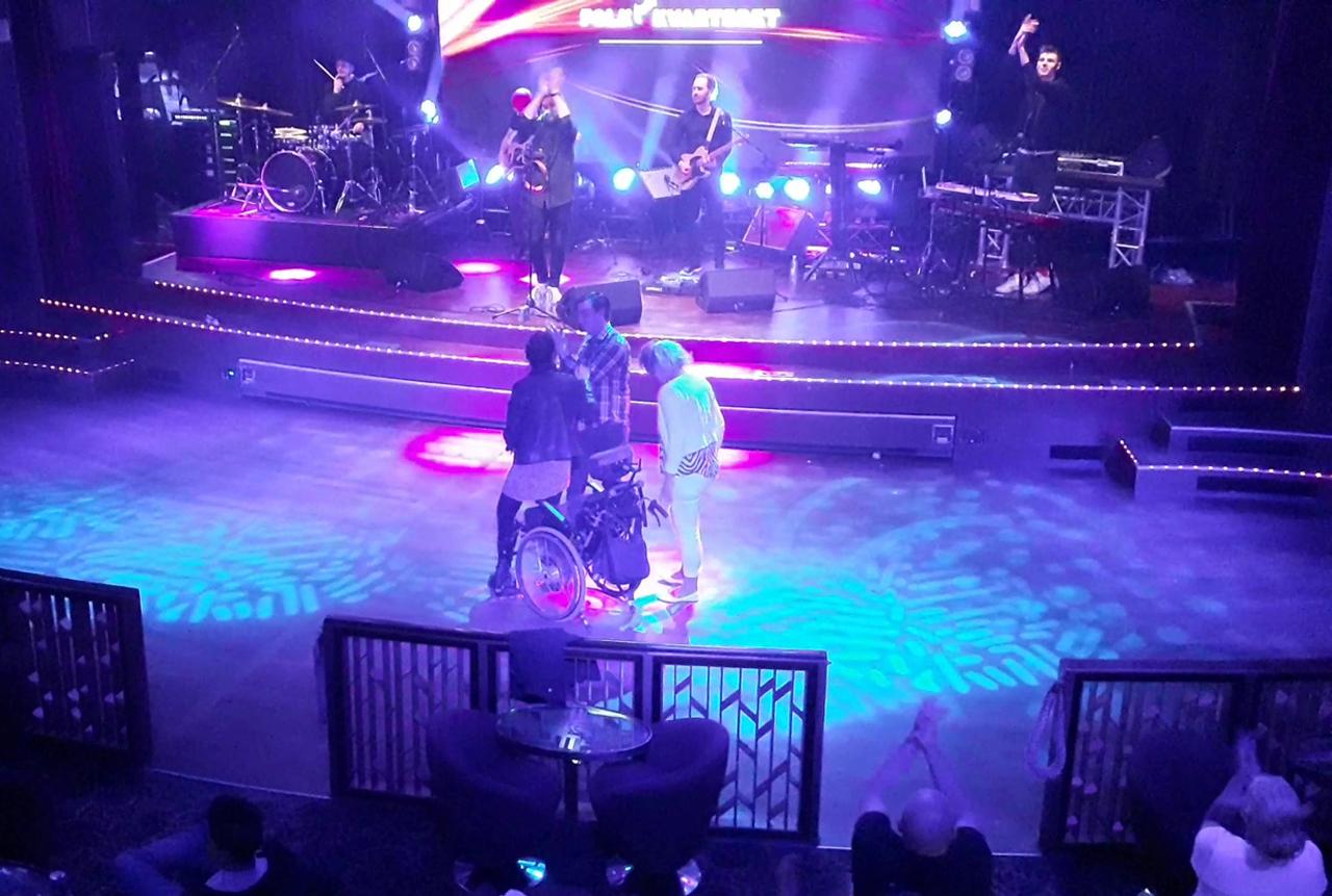 밴드가 연주를 마치며 스테이지의 장애여성과 그 보호자, 그리고 함께 한 청년에게 박수를 보내고 있다. 객석에서도 이들에게 박수를 보내 응원했다. (스웨덴 스톡홀름에서 핀란드 헬싱키로 향하는 크루즈 나이트클럽에서)
