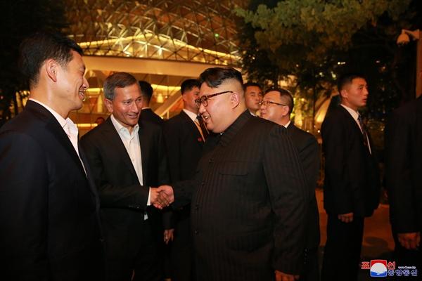 북한 노동신문, 김정은 싱가포르 명소 참관 보도 북한 노동당 기관지 노동신문은 12일 김정은 국무위원장이 전날 밤 싱가포르의 여러 명소를 참관했다고 보도했다. 사진은 자신의 한밤 투어를 안내한 싱가포르 정부 인사들과 인사를 나누는 김 위원장의 모습.