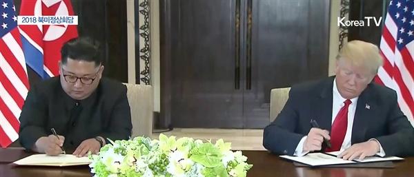 합의문에 서명하는 북-미 정상 역사적인 북미정상회담이 열린 12일 오후 싱가포르 센토사섬 카펠라호텔에서 김정은 국무위원장과 트럼프 대통령이 합의문에 서명하고 있다.