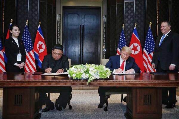 합의문 서명하는 김정은-트럼프 사상 첫 북미정상회담이 열린 12일 오후 싱가포르 센토사섬 카펠라호텔에서 김정은 국무위원장과 트럼프 대통령이 공동 합의문에 서명하고 있다. 김여정 부부장과 폼페이오 국무장관이 배석해 있다.