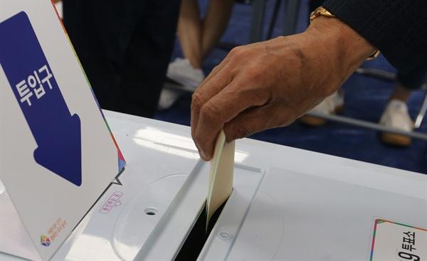 제7회 전국동시지방선거 투표일인 13일 충북 증평군 증평읍 제9투표소에서 한 유권자가 투표용지를 투표함에 넣고 있다.