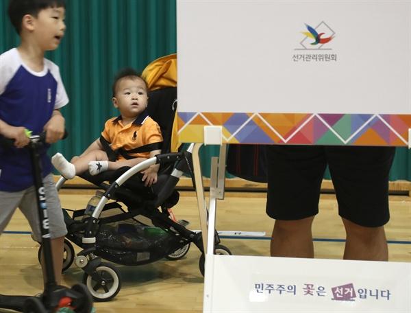 6.13 전국동시 지방선거가 실시된 13일 오전 서울 서초구 반포1동 제2 투표소가 설치된 원천중학교에서 아빠와 함께온 어린이들이 투표 모습을 보고 있다.