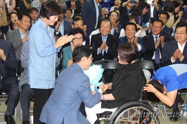 더불어민주당 김경수 경남도지사 후보가 당선이 유력시 된 14일 오전 1시경 선거사무소에서 휠체어를 탄 지지자로부터 꽃다발을 받고 있다.