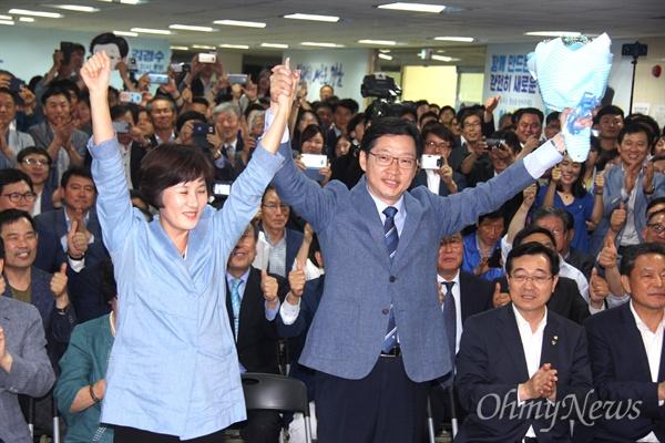 더불어민주당 김경수 경남도지사 후보가 당선이 유력시 된 14일 오전 1시경 선거사무소에서 부인과 함께 꽃다발을 받은 뒤 들어 보이고 있다.