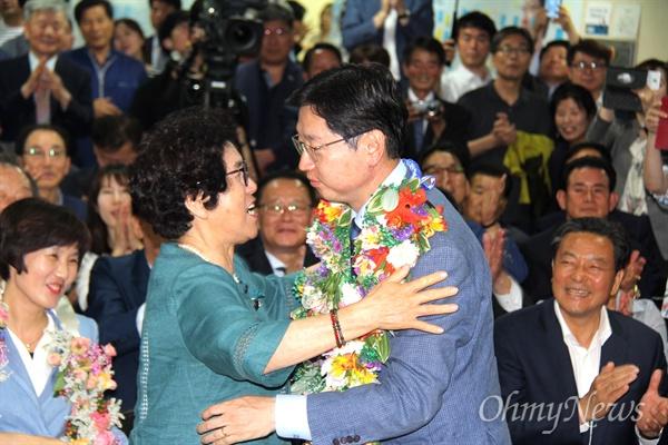 더불어민주당 김경수 경남지사 후보의 어머니가 14일 새벽 당선이 확실시 되자 선거사무소에서 아들을 안아주고 있다.