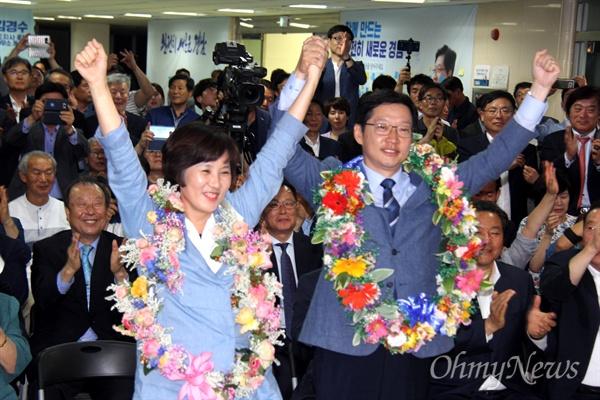 더불어민주당 김경수 경남지사 후보와 부인 김정순씨가 14일 새벽 당선이 확실시 되자 꽃다발을 목에 걸고 인사하고 있다.