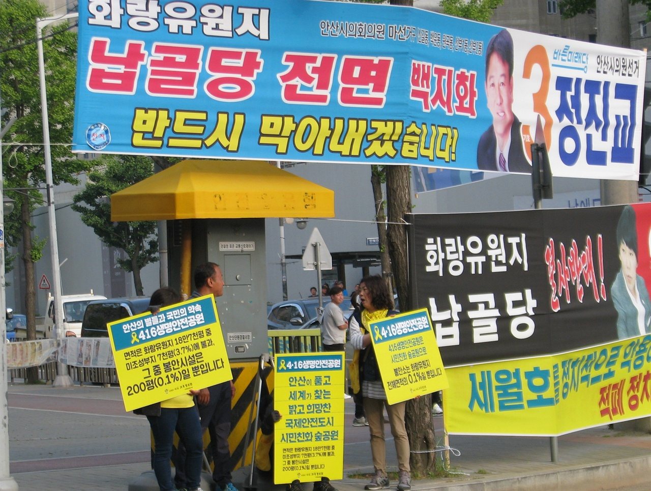 세월호 추모공원을 '납골당'으로 표기한 보수 야당 후보자들의 홍보물 앞에서 진실 알리기 캠페인을 펼치고 있는 세월호 유가족들