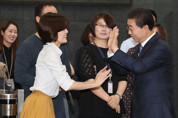 서울시장 3선에 성공한 박원순 시장(오른쪽)이 14일 오전 서울시청으로 출근하며 직원들과 하이파이브 인사를 나누고 있다.