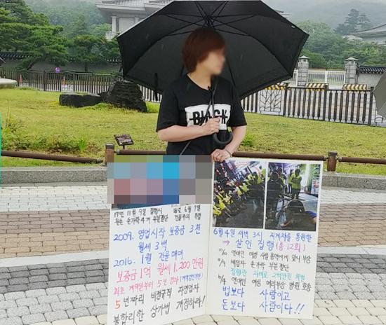 궁중족발 임차인 김씨의 아내 윤씨가 청와대 분수대 앞에서 1인 시위를 하고 있다. 윤씨는 '5년짜리 비정규직 자영업자, 불합리한 상가법 개정하라'라는 팻말을 세우고 있었다. (사진= 강규수)