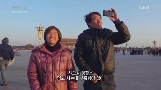 평생 마오쩌둥 사진 한 번 보는 게 소원인 쿤의 어머니(왼쪽)를 데리고 천안문 광장으로 간 쿤. 모자는 국가가 강조하는 '샤오캉 사회(물질적으로 안락한 사회)' 문구를 보며 희망을 품는다.