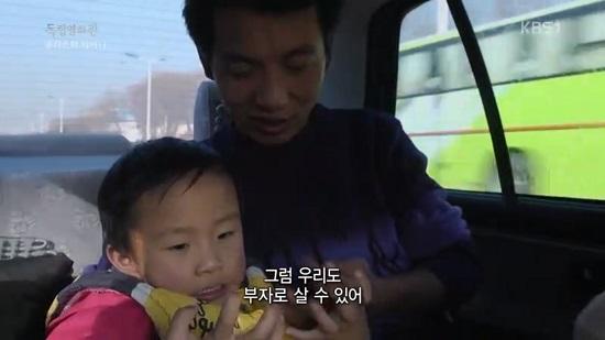 """쿤은 베이징 시내를 달리는 택시 안에서 네 살배기 아들 치치(왼쪽)에게 """"돈을 많이 벌어야 여기서 살 수 있다""""고 말한다."""