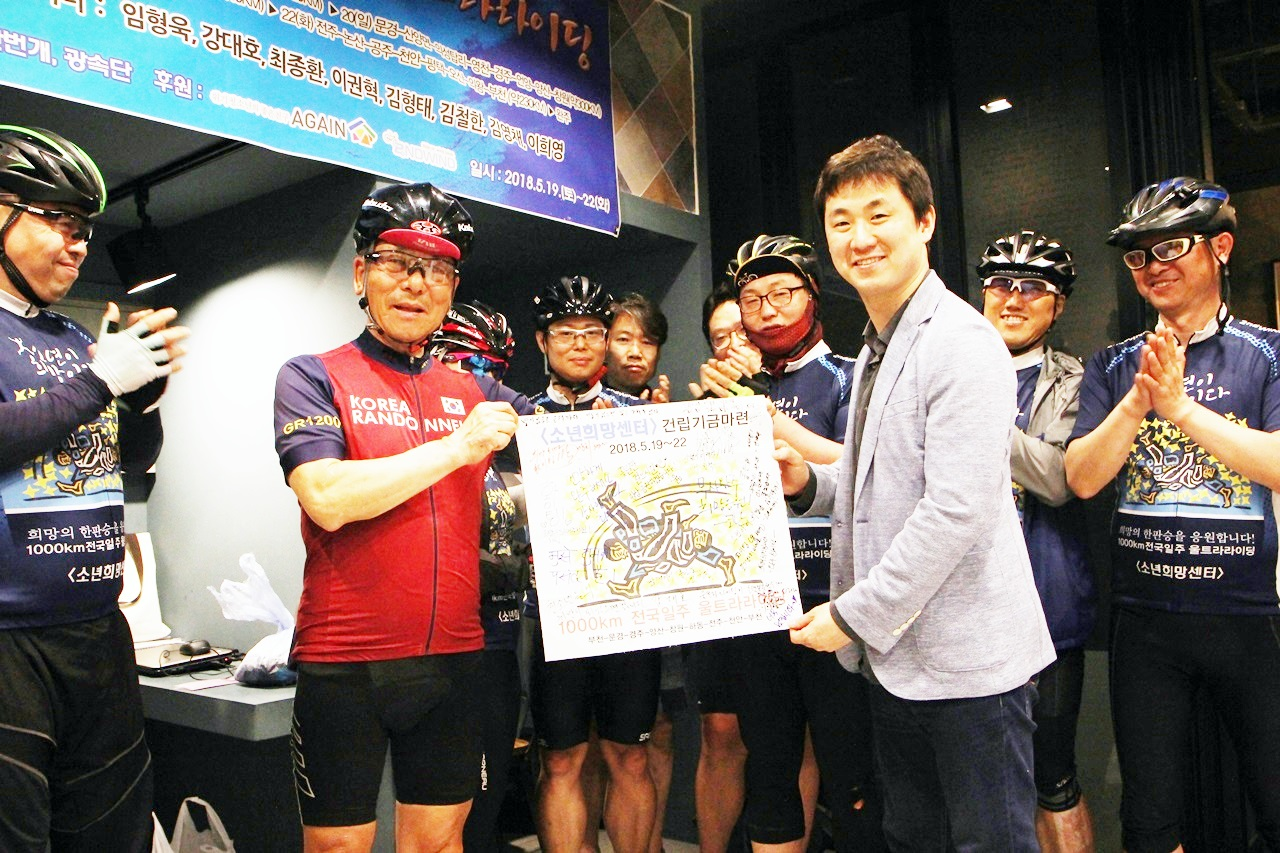 <소년희망센터> 건립기금 마련을 위해 1000km를 달린 라이더들로부터 응원 플래카드를 전달받고 있는 임진성 위원장.