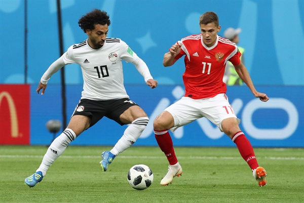 '너와 나 한폭의 데칼코마니' 19일 오후(현지시간) 러시아 상트페테르부르크 스타디움에서 열린 2018 러시아 월드컵 A조 러시아와 이집트의 경기. 이집트의 모하메드 살라흐와 러시아의 로만 조브닌이 볼다툼을 하고 있다.