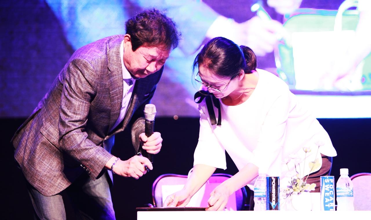 대전연극협회에서 기념으로 영구보관하기 위해 배우 윤문식의 액자사진에 사인을 받고 있다.