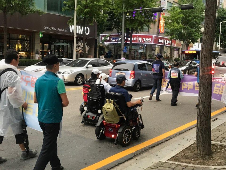 전동휠체어를 타고 행진을 이어가는 참가자들 전동휠체어를 타고 행진을 함께하고 있는 참가자들