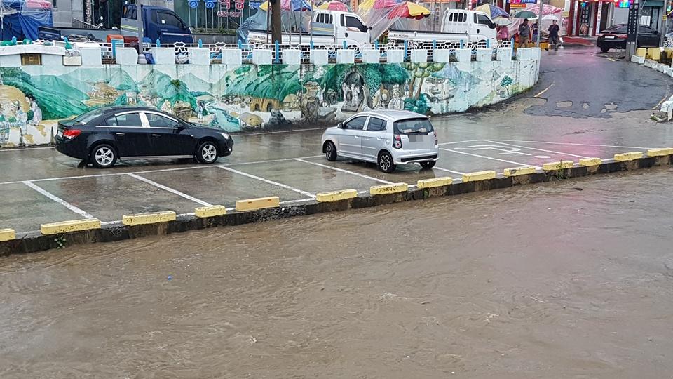 1일 7호 태풍 '쁘라삐룬'의 영향으로 장마전선이 북상하면서 강한 비가 내리는 가운데, 홍성천 하류 주변 주차장의 출입이 통제되고 있다. 이런 가운데 하천 범람위험으로 주차되어 있던 차량이 이동하고 있다.