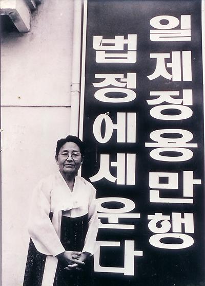 '태평양전쟁희생자 광주유족회' 이금주 회장이 유족회 사무실로 쓰고 있는 집 현판 앞에서 포즈를 취하고 있다.
