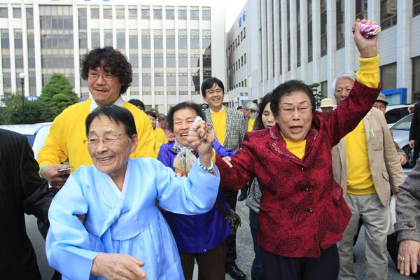 2013년 11월 1일 광주지방법원에서 승소 소식을 듣고 감격에 겨워 환호하는 이금주 광주유족회 회장과 양금덕 할머니 모습.