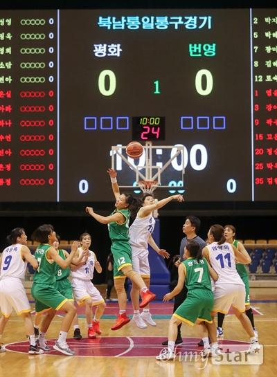 일 평양 류경정주영체육관에서 개최된 남북통일농구경기에서 여자 '평화'팀과 '번영'팀이 혼합경기에서 점프볼을 하고 있다.
