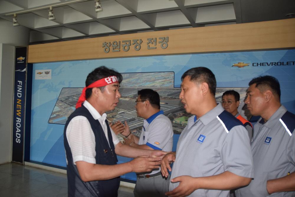 김선홍 본부장과의 면담을 요구한다 홍지욱 금속노조 경남지부장이 김선홍 한국지엠창원공장 본부장과의 면담을 요구하고 있다. 사측 관계인들이 막아섰다.